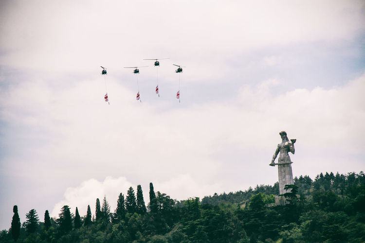 Low angle view of helicopters flying with flags by statue against sky