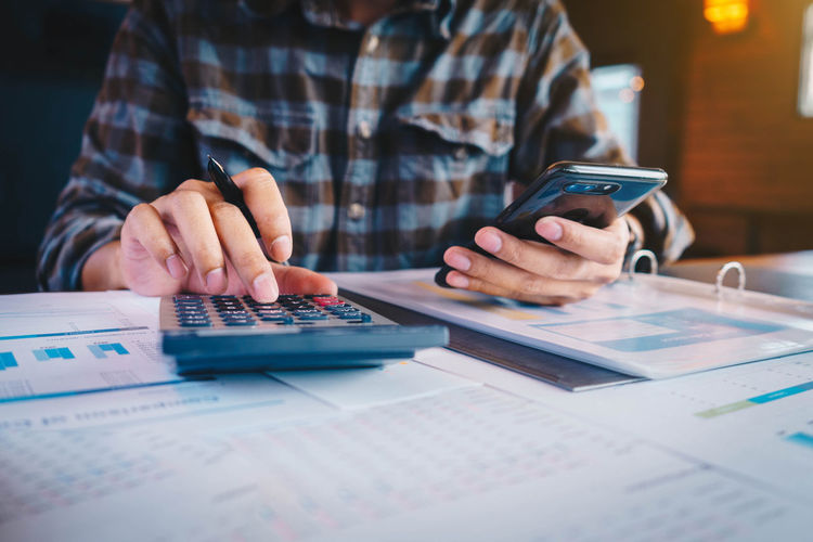 Midsection of businessman using calculator and mobile phone in office