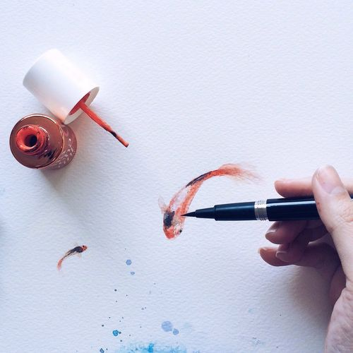 Close-Up Of Hand Painting On White Surface