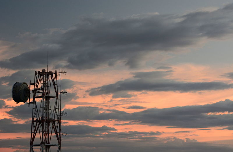 Low angle view of telephone pole against sky during sunset