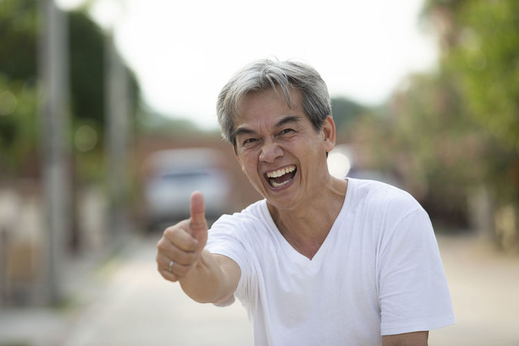 Portrait of mature man gesturing thumbs up while standing on street