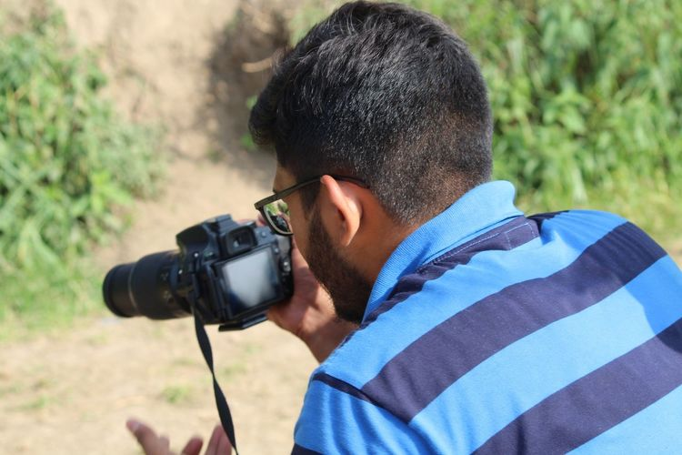 Rear view of man photographing with camera on field