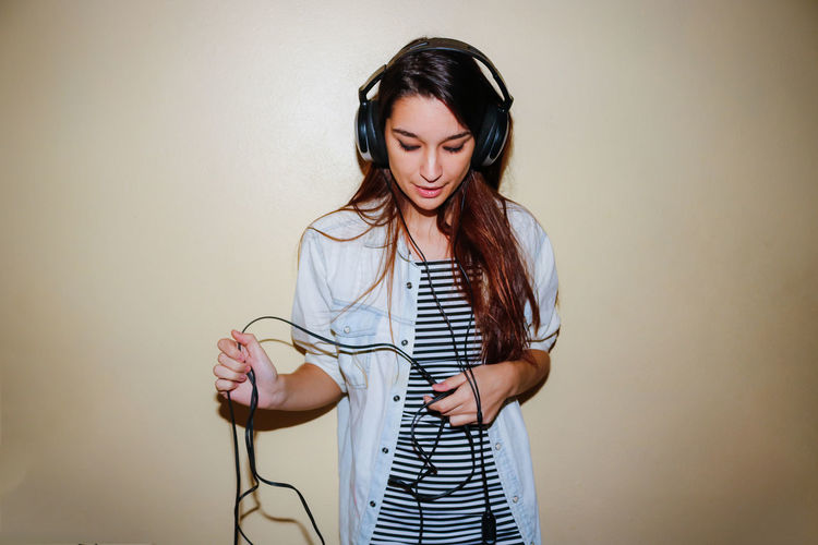 Woman wearing headphones while standing by wall