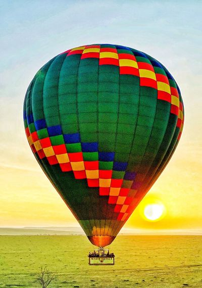 Multi colored hot air balloon flying over land