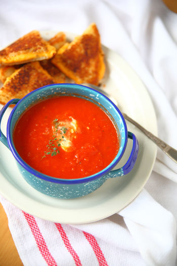 Tomato soup and grilled cheese vertical American Foods Bowl Close-up Comfort Food Day Dish Cloth Fabric Fresh Oregano Freshness Grilled Cheese Home Cooking Home Food Indoors  Lunch No People Overhead Ready-to-eat Red Snack Supper Tasty Textures Tomato Soup White Platter