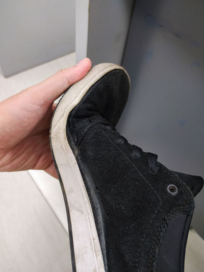 Low section of person holding shoe