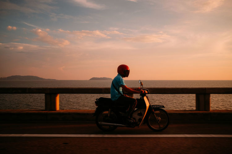 Man riding motor scooter by sea on bridge during sunset