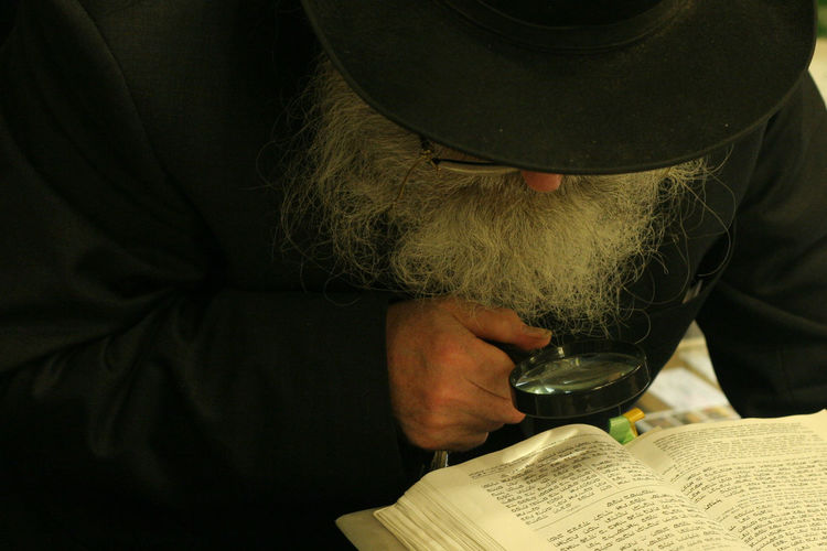 Detective reading book through magnifying glass