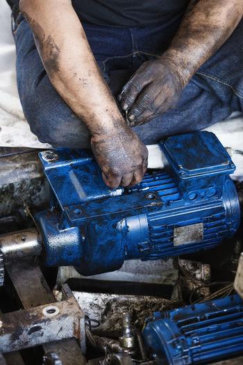 Close-up of man fixing machinery