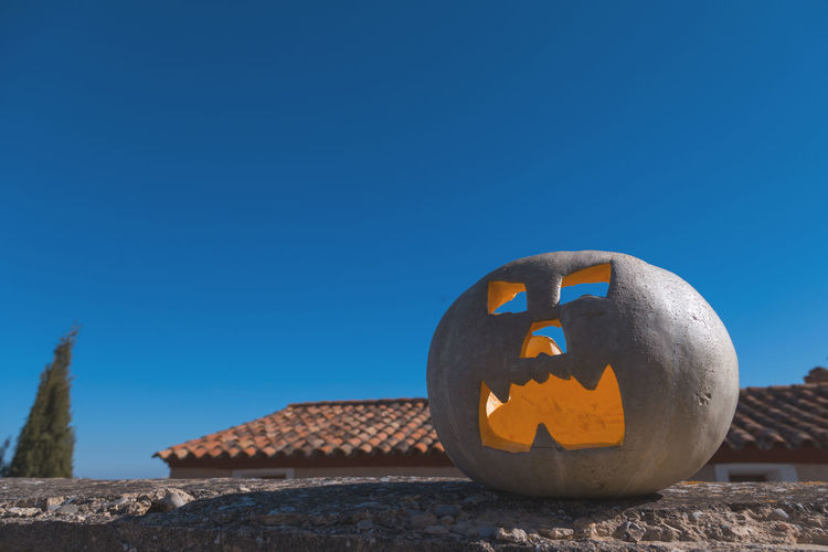 Low angle view of jack o lantern on retaining wall against clear blue sky
