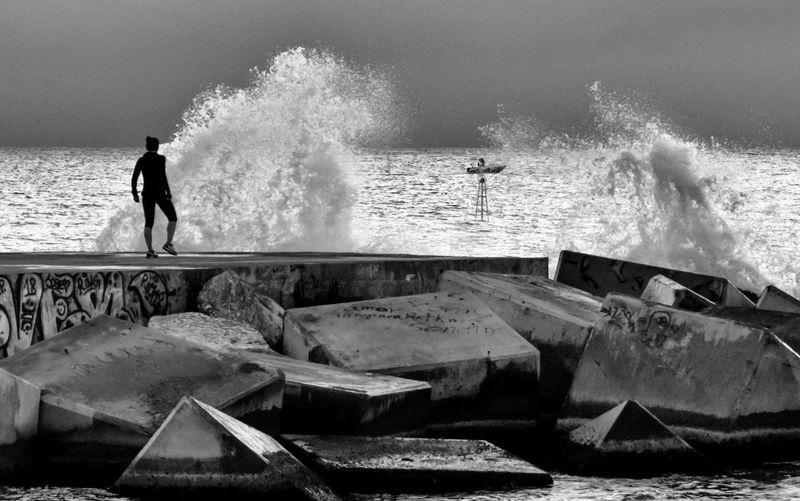 Silhouette woman walking on pier in sea