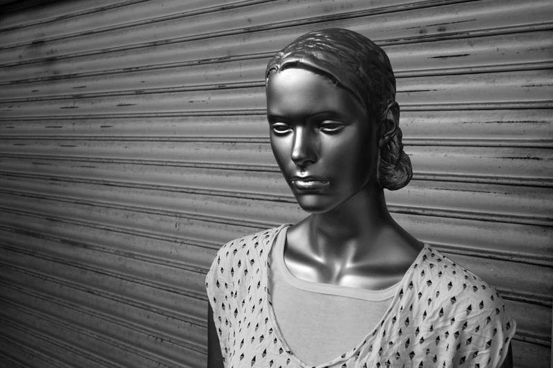 Mannequin in display against shutter