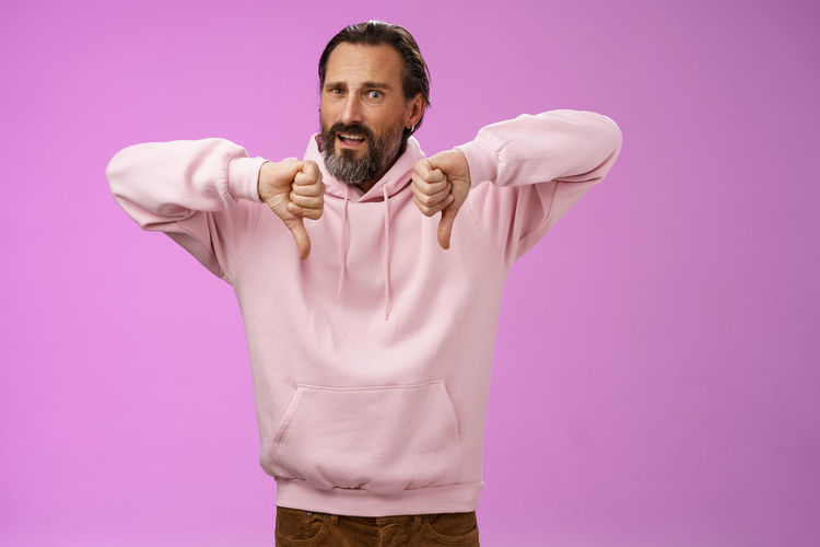 Portrait of man standing against pink background