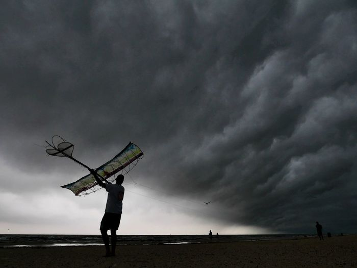 Low angle view of man standing on street against storm clouds