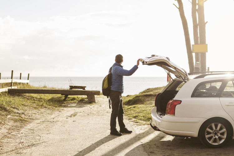 Rear view of man standing by car against sky