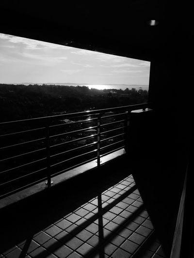 Silhouette railing against sky seen through window