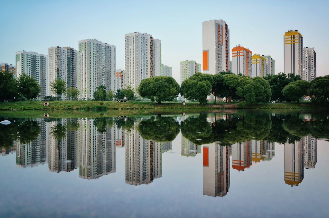REFLECTION OF MODERN BUILDINGS IN CALM LAKE AGAINST CLEAR SKY