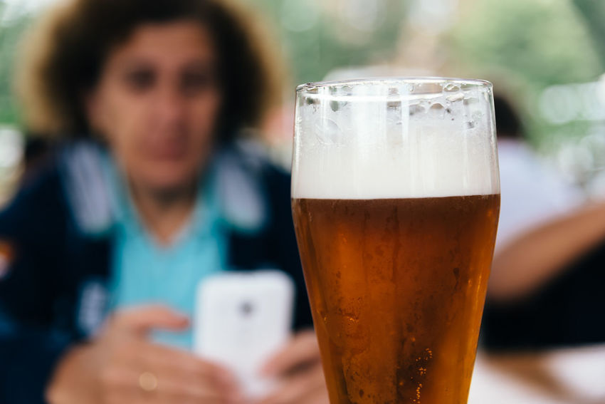 Close up of pint of lager beer against people Czech Lager Beer Adult Alcohol Beer Beer - Alcohol Beer Glass Close-up Drink Drinking Glass Focus On Foreground Food And Drink Front View Glass Household Equipment Indoors  Lager Lifestyles One Person Portrait Real People Refreshment Women