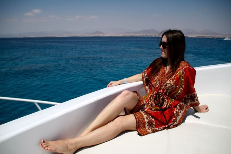 Young woman sitting in boat by sea against sky
