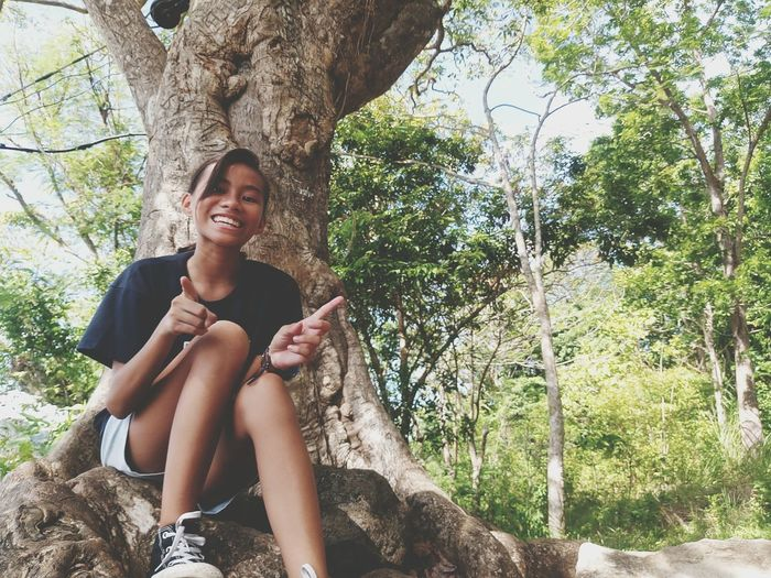 Portrait Of Cheerful Girl Sitting On Tree Trunk At Park