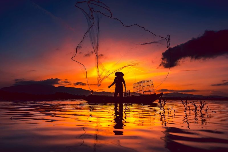 Silhouette fisherman standing in lake against sky during sunset