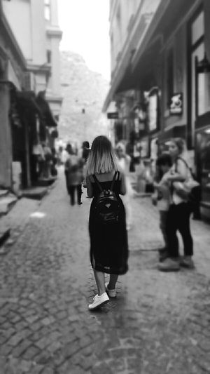 Street Walking Rear View Focus On Foreground Building Exterior Lifestyles Incidental People City Architecture Full Length Casual Clothing Holding The Way Forward Long Hair Person Streetphotography Taking Photos Black And White Girl Black And White Photography Narrow Day City Life Footpath Blackandwhite