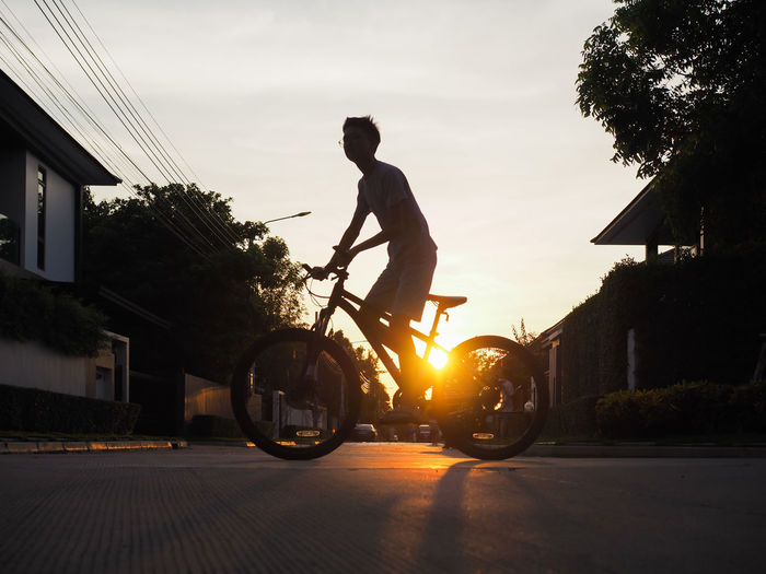 Man riding motorcycle on street against sky during sunset