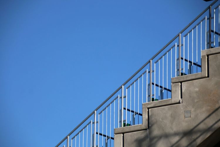 Low angle view of staircase by building against clear blue sky