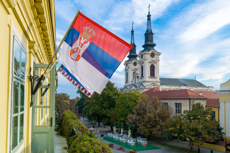Low angle view of flag amidst buildings in city against sky