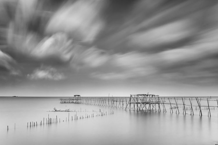 Abandoned Pier In Sea Against Sky