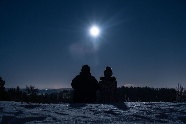 Rear view of silhouette people sitting on snow covered field against sky