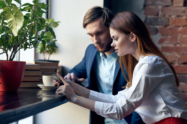 Young businesswoman and businessman looking at mobile phone at cafe
