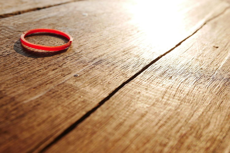 Plastic band on wooden desk Plastic Band Close-up Day Indoors  Love No People Red Table Wood - Material Wooden