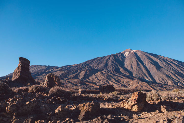 Scenic view of volcanic mountain against clear blue sky