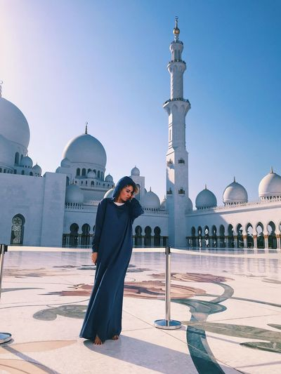 Woman standing at grand mosque against clear blue sky