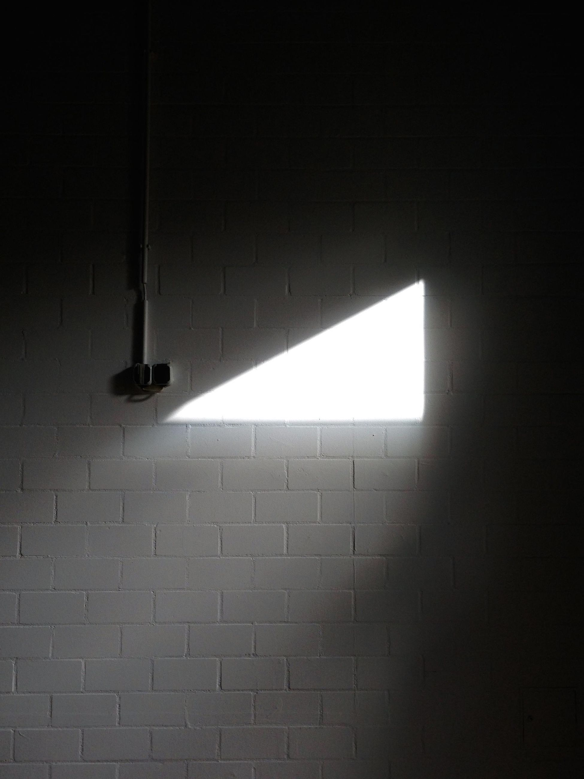 wall - building feature, illuminated, brick, brick wall, architecture, wall, lighting equipment, no people, built structure, indoors, sunlight, glowing, low angle view, electric light, light, light - natural phenomenon, hanging, pattern, electricity, ceiling, fluorescent light, electric lamp, light fixture