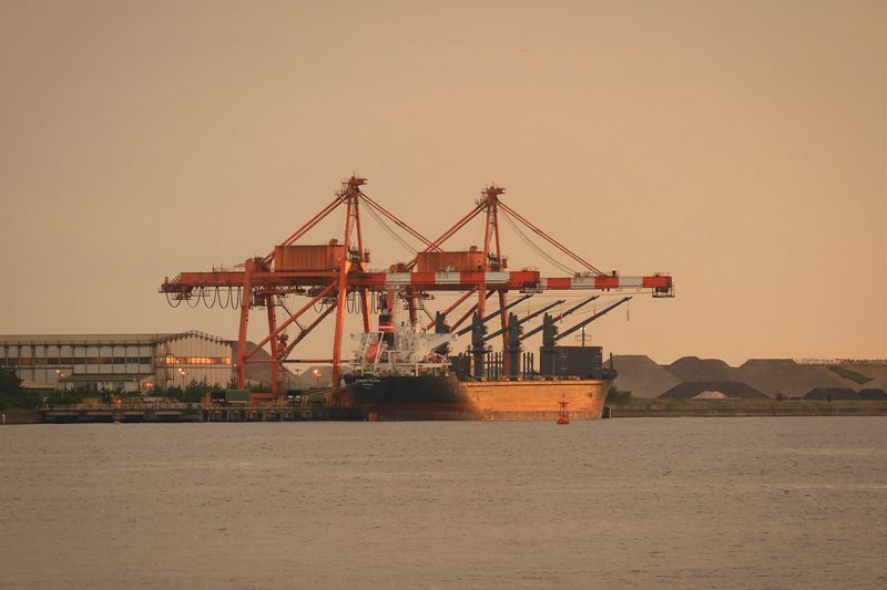 Calm sea with cranes in distance against clear sky