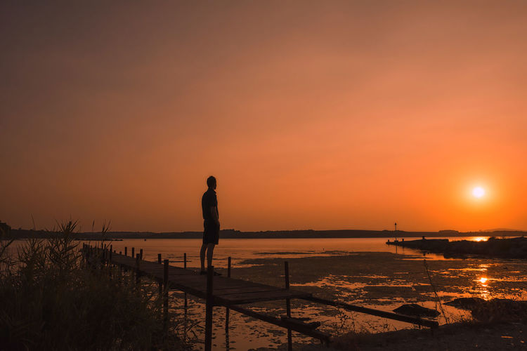 Rear view of silhouette man looking at sea against dramatic sky during sunset