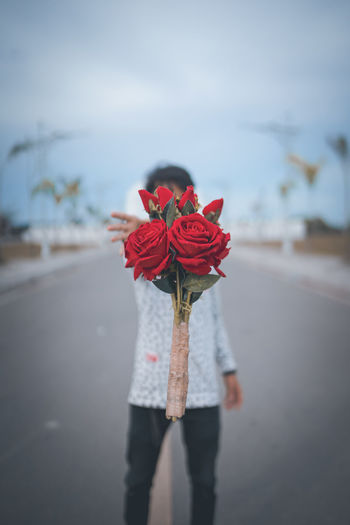 Rear view of woman standing on red rose