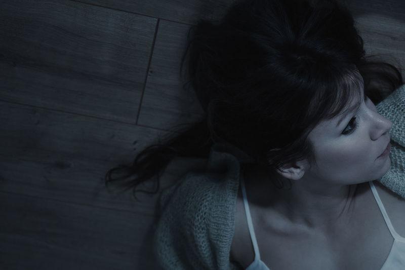High Angle View Of Mid Adult Woman Lying On Hardwood Floor At Home
