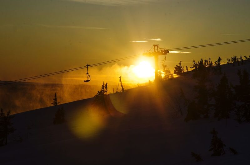 Silhouette of ski lift during sunset