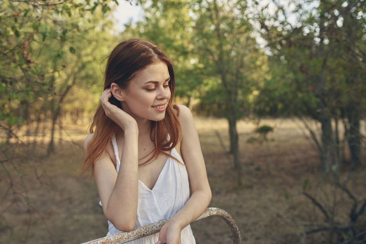 Young woman smiling against trees