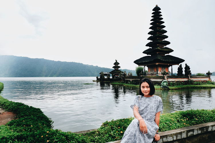 Portrait of young woman sitting against pagoda in lake