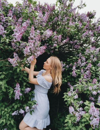 Beautiful woman standing by pink flowering plant