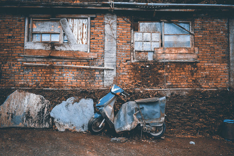Abandoned scooter and building in city