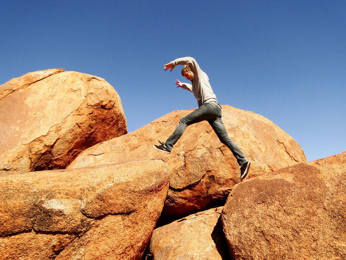 Low angle view of man jumping on rocks against clear blue sky