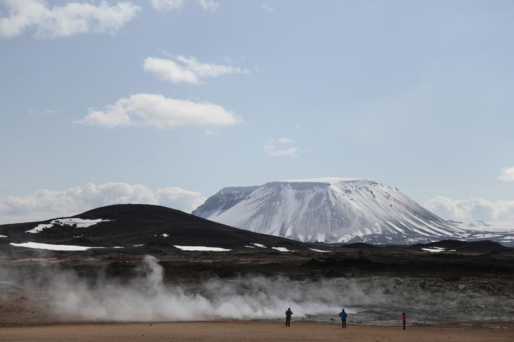 People at volcanic landscape by mountains against sky