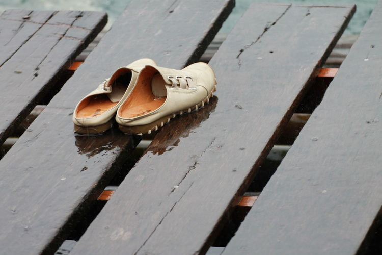 Shoes on wet wooden pier