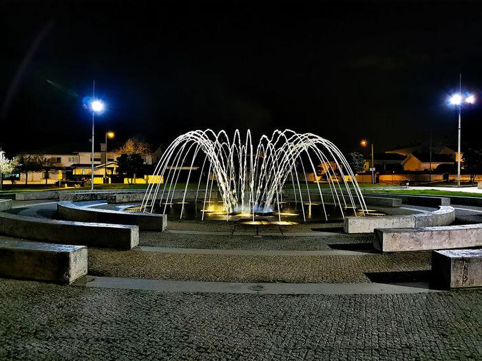 Illuminated ferris wheel by city against sky at night