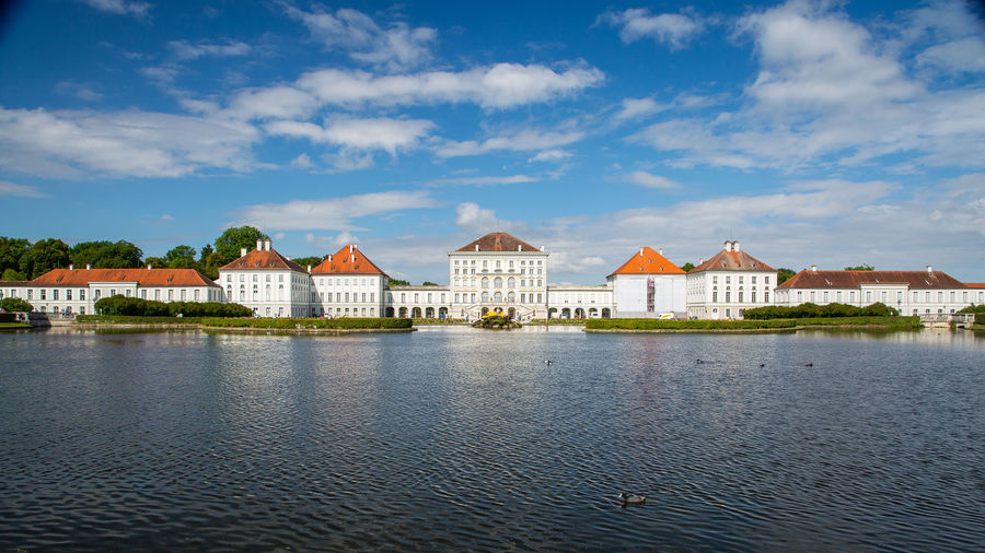 Nymphenburg palace by lake against sky in city